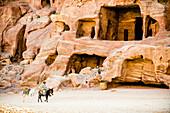 Mann reitet auf einem Esel vor Höhlengräbern, Petra, Jordanien, Naher Osten