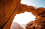 Woman hiking along Jabal Umm Fruth Rock Bridge, Wadi Rum, Jordan, Middle East