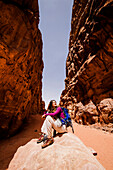 Woman resting on a stone in a gorge, Wadi Rum, Jordan, Middle East