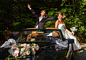 bridal couple have fun with their cabriolet, Bavaria, Germany