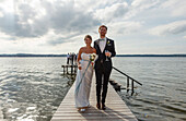 Bridal couple is walking along the jetty, Starnberger See, Bavaria, Germany