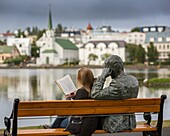 Woman reading next to statue of an Icelandic poet, Tomas Gudmundsson, Reykjavik, Iceland The city of Reykjavik has been designated as a UNESCO city of literature