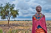 Kenya Africa Amboseli Maasai tribe village Masai woman in red costume dress and beads and tree in remote area of Amboseli National Park safari 1