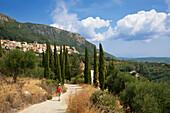 Woman hiking towards the mountain village of Lakones, above Paleokastritsa, Corfu island, Ionian islands, Greece