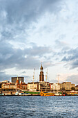 View over river Elbe to Landungsbruecken and church St. Michael in sunset, Hamburg, Germany