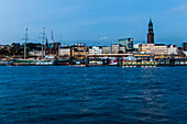 View ove river Elbe to Landungsbruecken and church St. Michael in the evening, Hamburg, Germany