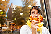 Frau isst eine Belgische Waffel, Lüttich, Wallonien, Belgien