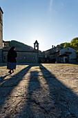 Nun at Santa Maria degli Angeli, church with bell tower and shadow, La Verna, Franciscan monastary, Monte Penna, St. Francis of Assisi, Via Francigena di San Francesco, St. Francis Way, near Chiusi della Verna, province of Arezzo, Tuscany, Italy, Europa
