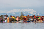 Venetian Lagoon and the Island of Burano, Fishing village with colourful house facades, Snow-capped mountains of the Alps in the background, Veneto, Italy
