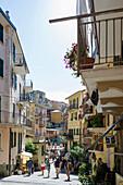 Tourists walking along a lane, Manarola, Riomaggiore, Cinque Terre, La Spezia, Liguria, Italy