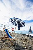 Deck chair and sunshades at coast, Bagni Scogliera, Nervi, Genoa, Liguria, Italia