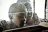 Two boys looking through a window, Malawi, Africa