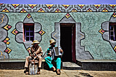 Two men of the Basotho tribe playing music in front of their house with traditional facade paintings, South Africa, Africa