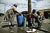 A woman and two children at the public water tab, Langa township, Cape Town, South Africa, Africa