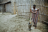 Young mother from the Lozi tribe with baby pounding grain in a big wooden mortar, Caprivi region, Namibia, Africa