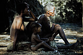 Mother, daughter and granddaughter of the San tribe sitting on the ground in front of their hut, Otjozondjupa region, Namibia, Africa