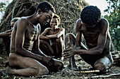 Men from the San tribe igniting a fire with two wooden sticks, Otjozondjupa region, Namibia, Africa