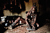 Woman of the Himba tribe in her hut preparing food, Kaokoland, Namibia, Africa