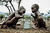 Two children of the Himba tribe eating out of a pot, Kaokoland, Namibia, Africa