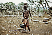 Child of the Himba tribe carrying a pot, Kaokoland, Namibia, Africa