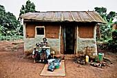 Woman sewing in front of her hut, Buwenda, Uganda, Africa