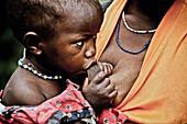 Child from the Pygmy tribe feeding from her mother's breast, Lake Bunyonyi, Uganda, Africa