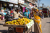 Two women at a fruit stand in the city center, Porbandar, Gujarat, India