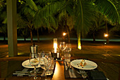 Candlelight dinner on the beach with palm trees at Hotel Jetwing Blue, Negombo, Sri Lanka