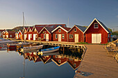 Boats and boot houses in Bleket port with reflection in the water, Tjoern Island, Province of Bohuslaen, West coast, Sweden, Europe