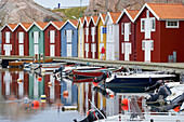 Boats and boat houses in the port of Smoegen, Reflection in the water, Sotenas Peninsula, Province of Bohuslaen, West coast, Sweden, Europe
