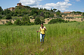 Woman nordic walking through a field at the foot of the Vinery Palazzo Massani, near San Quirico d'Orcia, Toskana, Italy, Europe