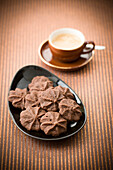 A cup of espresso and a dish of cookies