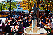 Beer garden and Weiss Ferdl Fountain at Viktualienmarkt, Munich, Upper Bavaria, Bavaria, Germany