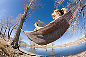 Young woman writing in journal while resting in hammock in Bishop, CA Bishop, California, USA