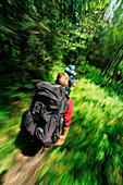Blur motion view of a backpacker in a lush forest North Carolina, USA