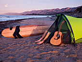 A young man lying in his tent with a guitar while camping on the beach waiting for surf Carpinteria, California, USA