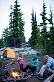 Two adult women and a little girl relaxing near a campfire in the evening while camping Montana, USA