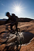 Mountain biker riding on the slickrock trail in Moab, Utah. (motion blur), Moab, Utah, USA