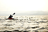 The silhouette of a male kayaker paddling across Flathead Lake, Montana, just before sunset Bigfork, Montana, USA