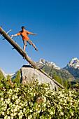 A young man hiker balances on an old log at the Grand Teton National Park, Wyoming Wyoming, USA