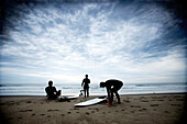 Three surfers on the beach getting ready to go surfing Ventura, California, USA