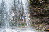Three young girls explore behind a waterfall Alberta, Canada
