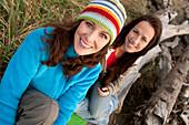 Two beautiful women smile while enjoying the sunset at La Push Beach, from a drift log La Push, Washington, USA