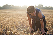 Male runner in his late 20's catches his breath as he finishes his run it an open field in San Diego, California San Diego, California, USA