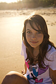 A pre-teen girl looks up at the camera and smiles at Paia Beach, Maui, Hawaii as the sun rises Maui, Hawaii, USA