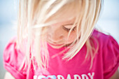 Select focus of a cute young blonde girl looking down at her pink shirt Oceanside, California, USA