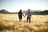 Couple hold hands, look as the camera and smile in an open field, San Diego, California, USA