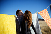 Couple kiss near colorful fabrics hung on a clothes line San Diego, California, USA