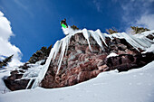 A male snowboarder jumps off an ice waterfall cliff on a sunny day in Colorado Vail, Colorado, USA