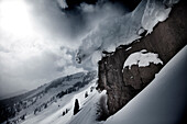 A snowboarder does a half cab off a cliff on a stormy powder day in Colorado Vail, Colorado, USA